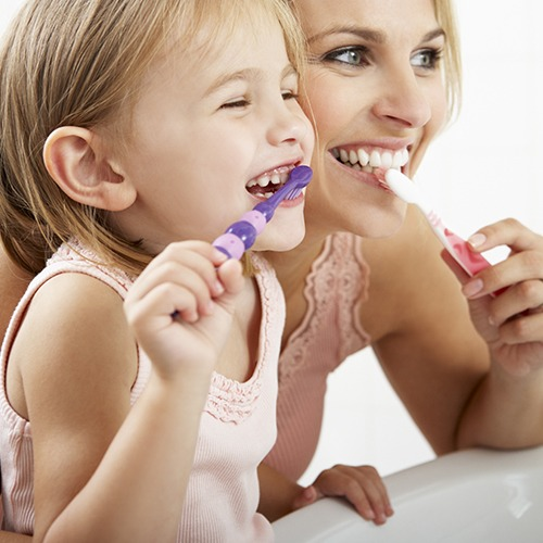 Mother and daughter brushing teeth to prevent dental emergencies