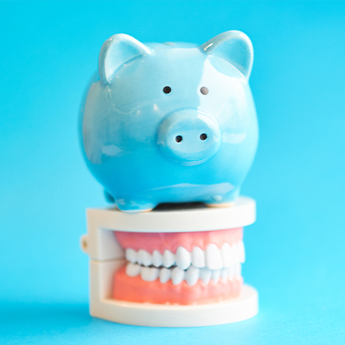 Piggy bank sitting on top of a model set of teeth