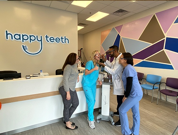 The Happy Teeth of Levittown dental team and dentist at the front desk