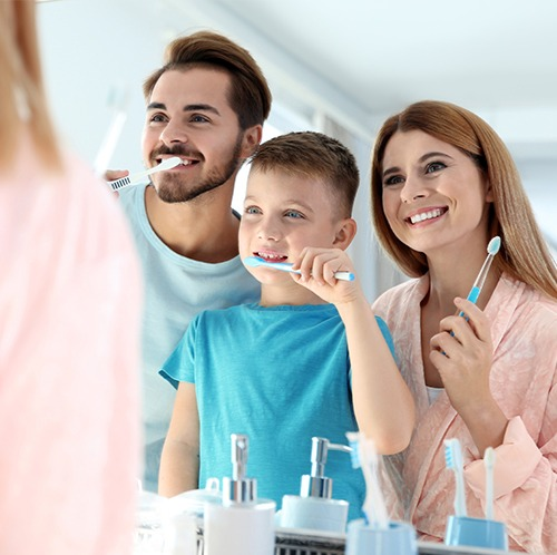 Mother father and son brushing teeth together