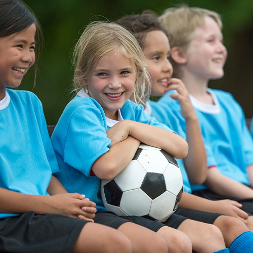 Little girl holding soccer ball with healthy smile after silver diamine fluoride treatment
