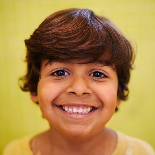 Child sharing healthy smile after pulp therapy