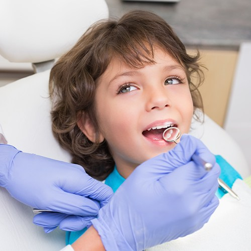 Dentist checking child's tooth colored fillings