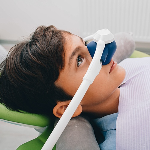 Child with nitrous oxide sedation dentistry mask in place during dental visit