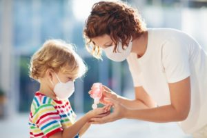 mom giving hand sanitizer to child, both wearing face masks