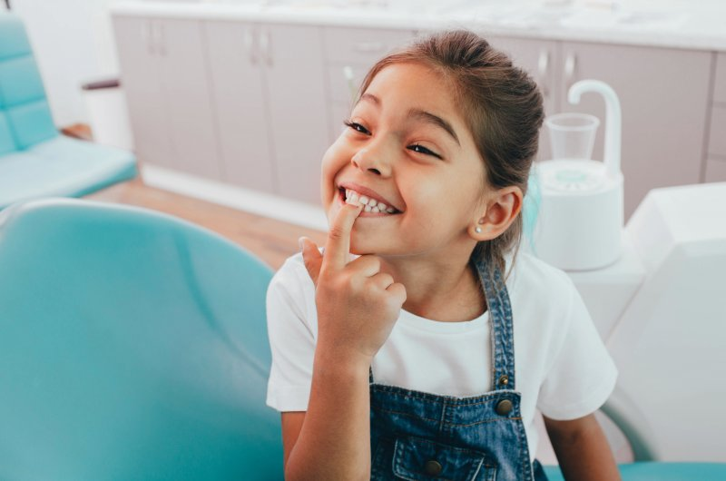 Child smiling and pointing to her teeth at dentist appointment