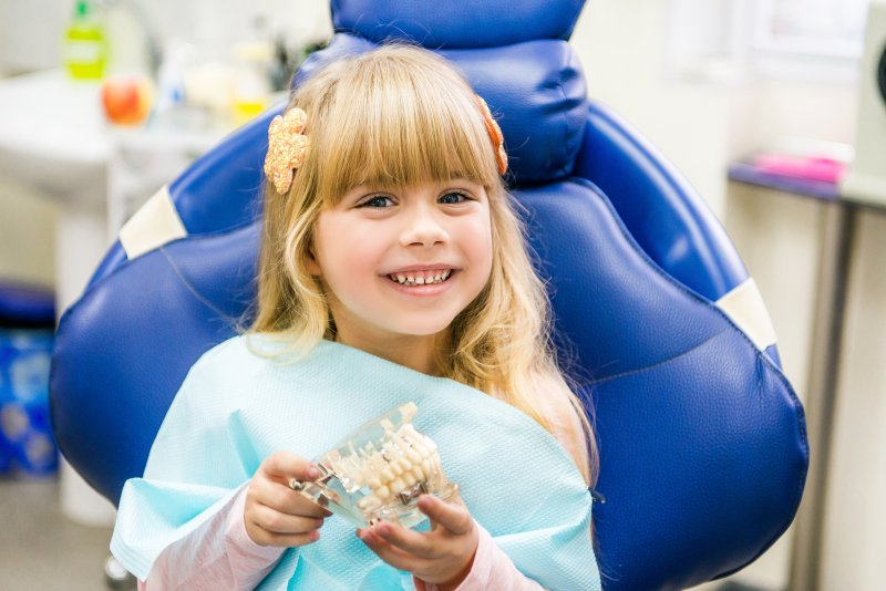 a little girl smiling while holding a mouth mold and seeing her pediatric dentist in Levittown
